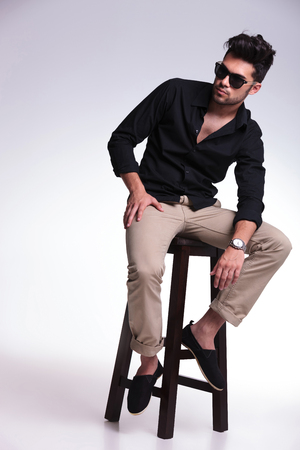 full length portrait of a young fashion man sitting on a chair and looking at his side, away from the camera while holding his elbow on his leg. on a light background photo