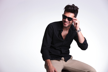 young fashion man sitting on a chair and adjusting his sunglasses while smiling and looking away from the camera. on a light background photo