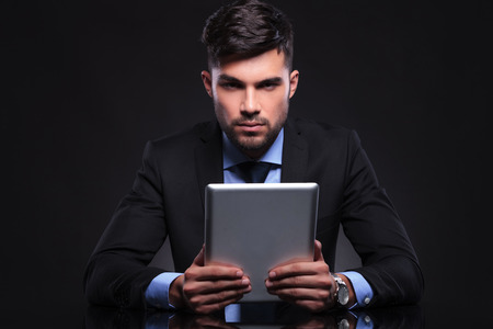 young business man holding a tablet with both hands and looing into the camera. on black background photo