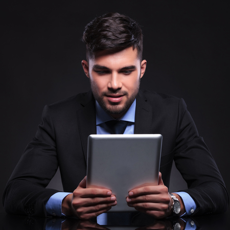 young business man looking at his tablet. on black background photo
