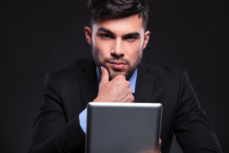 young business man looking pensively into the camera while holding a tablet and his hand on his chin. on black background photo
