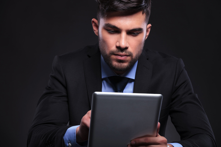 young business man working concentrated on his tablet. on black background photo
