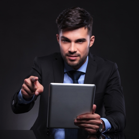 young business man holding his tablet and pointing at the camera. on black background photo