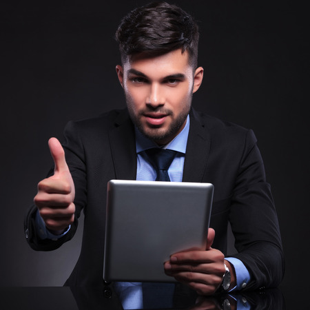 young business man holding a tablet and showing thumbs up gesture while looking into the camera. on black background photo