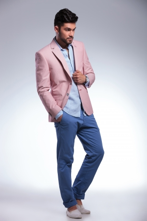 unshaved: full length portrait of a young casual man holding a hand on his pink jacket and one in his pocket while looking away from the camera. on gray background