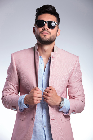 lapels: young casual man looking into the camera with both hands on his jacket. on gray background