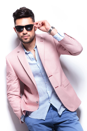 young casual man adjusting his sunglasses while holding a hand in his pocket and looking into the camera. on white background photo