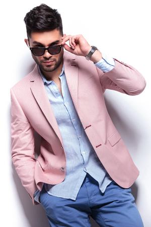young casual man taking off his sunglasses and looking into the camera while holding his hand in his pocket. on white background Stock Photo - 22200652