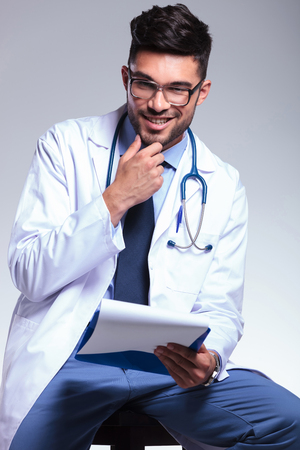 seated young male doctor holding a clipboard and touching his chin while smiling for the camera. on gray background Stock Photo - 22200576