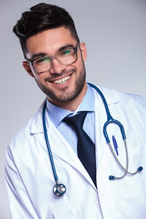 closeup portrait of a young male doctor smiling for the camera. on gray background photo