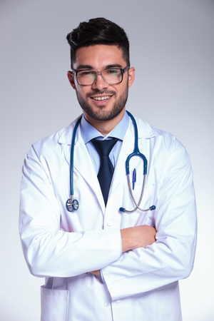 young male doctor smiling for the camera while holding his hands crossed. on gray background photo