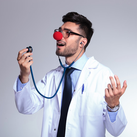 goofing: young male doctor listening himself sing at the stethoscope while wearing a clown red nose. on gray background