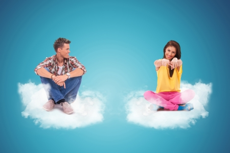 two young people sitting on clouds, woman pointing her finger to the camera photo