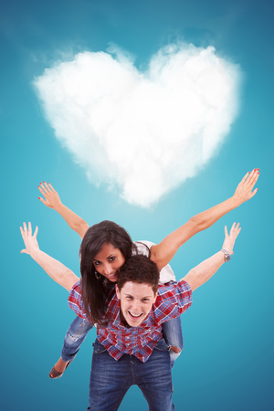 flying man: Handsome casual young man carrying his girlfriend on his back, playing in front of a heart shaped cloud