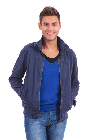 happy young casual man standing with hands in his pockets  photo