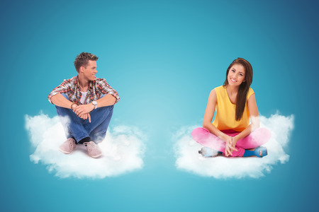 blue sky thinking: two young casual people sitting and resting on couds, man looking at woman and woman looking at the camera