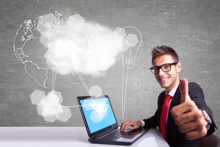 vue de c�t� d'un jeune homme d'affaires travaillant � son ordinateur portable et de rendre les thumbs up signe ok lors de la connexion � internet et le monde photo