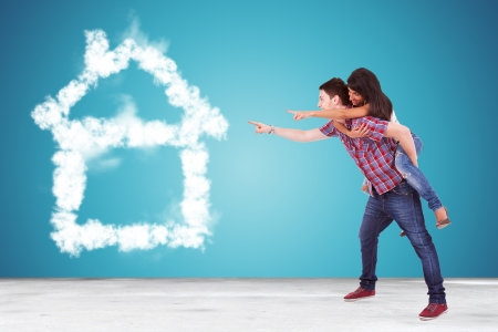 side view of a couple pointing to thier dream house made of clouds  photo