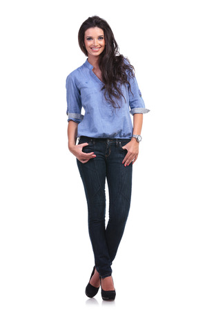 full length picture of a young casual woman standing with both thumbs in pockets and smiling for the camera.  photo
