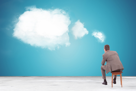 back view of a pensive business man looking at a speech bubble made of clouds photo