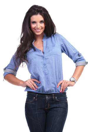 young casual woman smiling for the camera while holding both hands on her hips.  photo