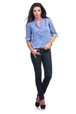 full length portrait of a young casual woman holding a thumb in a loop of her jeans while looking into the camera.  photo