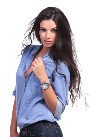 young casual woman posing with her hand on her shirt while looking into the camera.  photo