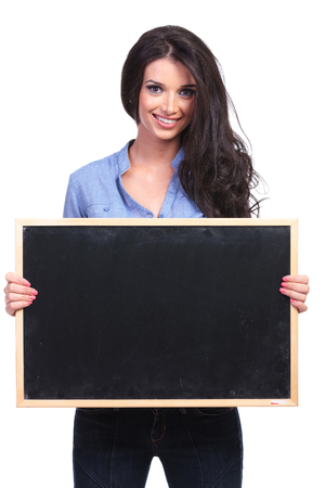 young casual woman holding a blackboard in her hands while smiling for the camera.  photo