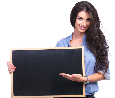 closeup of a young casual woman holding a blackboard and presenting on it while smiling for the camera.  photo
