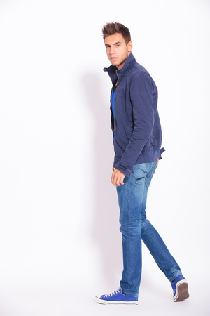 back to camera: full body picture of a casual man in jeans and jacket turning and looking at the camera, back view