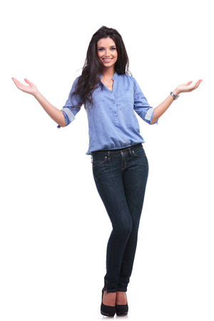 full length portrait of a young casual woman welcoming you with a smile on her face.  photo