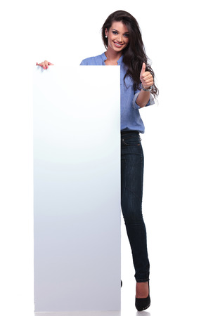 pannel: full length picture of young casual woman holding a big empty pannel and showing thumb up to the camera while smiling.