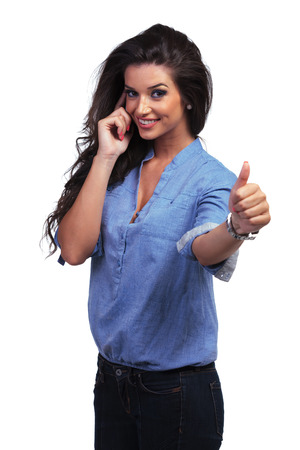 young casual woman showing the thumb up gesture while speaking on the phone.  photo