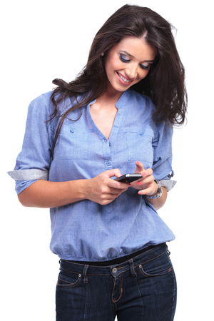 young casual woman looking at her phone and smiling.  photo