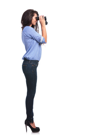 full length side view of a young casual woman looking away through binoculars.  photo