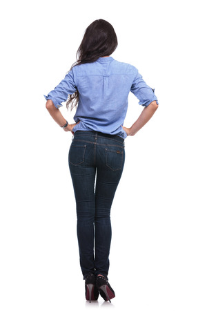 full length back view of a young casual woman holding her hands on her hips.  photo