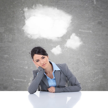 pensive young business woman at her desk with clouds as speech bubble photo