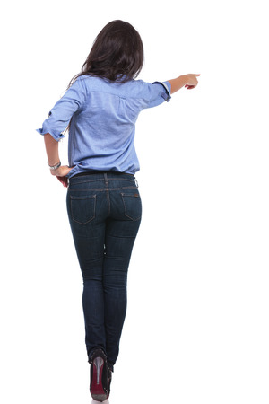 back view of a young casual woman pointing away from the camera with a hand on her hip. photo