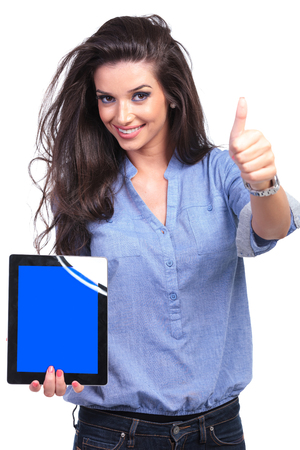 young casual woman presenting a tablet with a blue screen while showing the thumb up sign with a smile for the camera.  photo