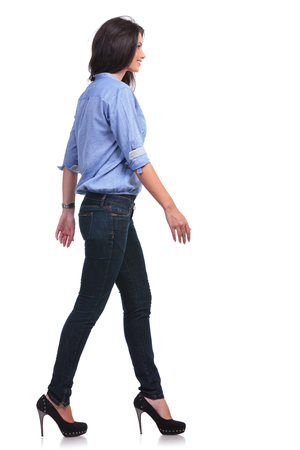 full length side view picture of young casual woman walking in front of the camera while looking forward. photo