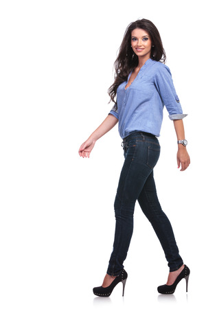 full length side view of a young casual woman walking forward while looking into the camera.