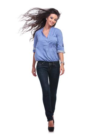 volle lengte foto van een jonge toevallige vrouw lopen naar de camera en glimlachen terwijl wegkijken.