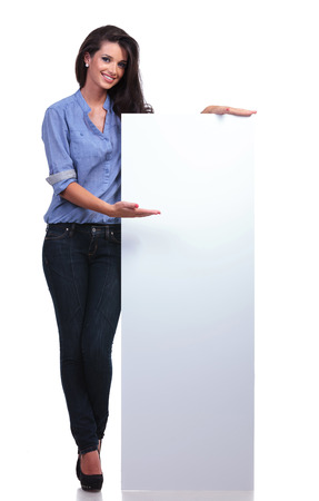 pannel: full length picture of a young casual woman presenting a blank pannel and smiling for the camera.  Stock Photo