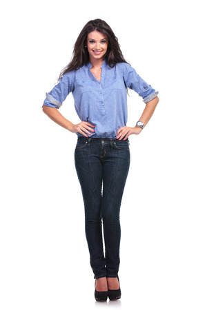 girl in jeans: full length picture of a young casual woman holding both of her hands on her hips and smiling for the camera.