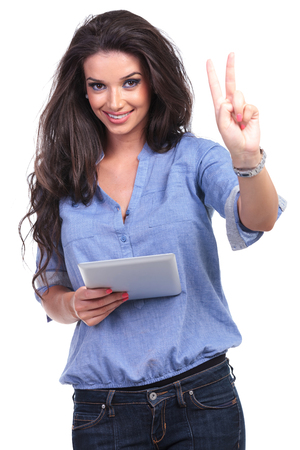 attractive gorgeous: young casual woman holding a tablet and showing the victory gesture with a smile for the camera.  Stock Photo