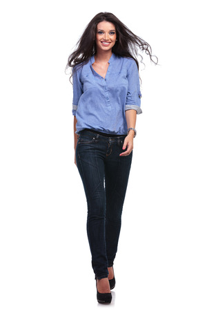 toward: full length picture of a young casual woman walking toward the camera and smiling.  Stock Photo