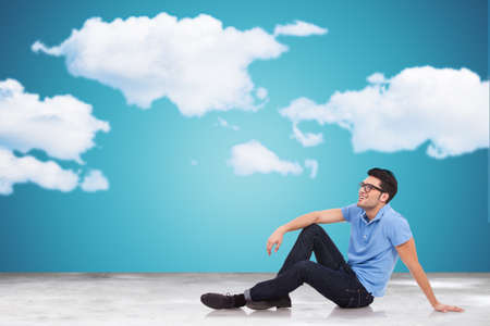 Handsome casual young man laying on the floor and looking away to clouds photo