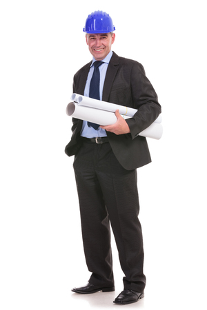 full length picture of a senior engineer holding some blueprints and his hand in his pocket while smiling to the camera. photo