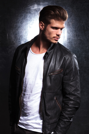 side view of a serious young fashion model in leather jacket looking away from the camera 免版税图像