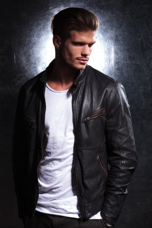 coats: smiling fashion man wearing a leather jacket looking away from the camera, side view picture Stock Photo